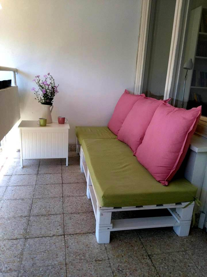 white painted pallet bench with green cushion and pink pillows