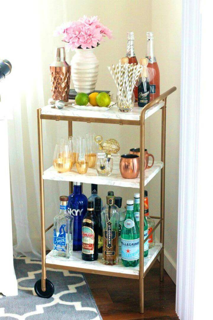 Make Marble and Gold Bar Cart Under $10, cover the surfaces of a card with marble contact paper to get faux marble surfaces and shelves in it!