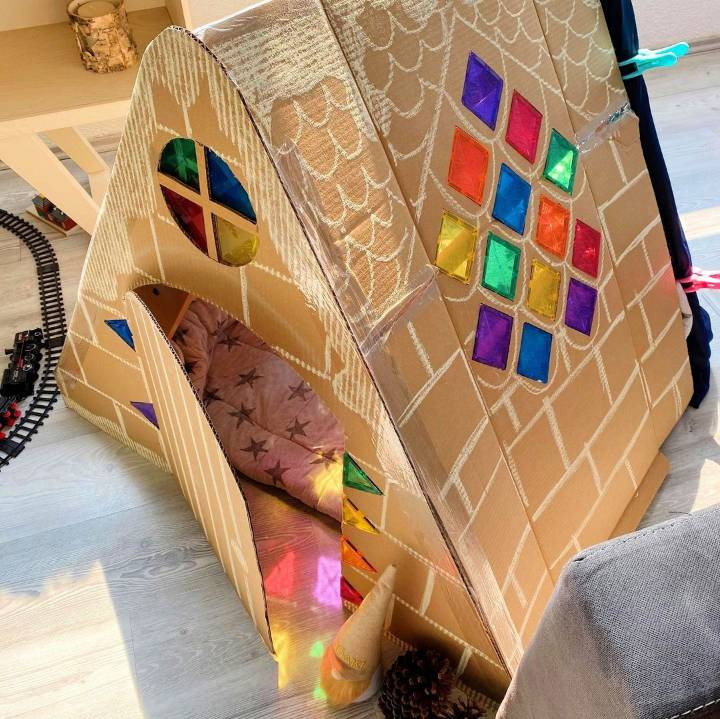 simple kids playhouse of cardboard box with a blanket